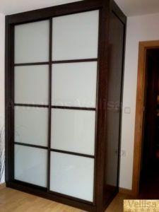 Armario empotrado en dormitorio principal. 245 X 158 X 72 Puertas correderas: 2 Con un costado visto en lado derecho. Modelo: Japonés, con tres junquillos horizontales separando cristal gris claro en 4 partes. Color base: Wengué, melamina