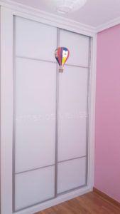 Armario empotrado en habitación juvenil. 253 X 141 X 67 2 puertas correderas con dos junquillos de aluminio mate, separados entre ellos 3/5 partes. Y enmarcado puertas aluminio mate, resto; cristal blanco con molduras en blanco, melamina